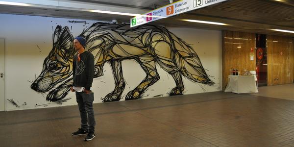 Straatkunstenaar DZIA poseert naast zijn kunstwerk van een vos.