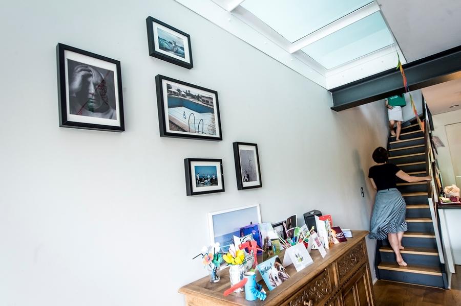 Een vrouw wandelt de trap op naar de eerste verdieping. We zien vooral het plafond van het gelijkvloers waarin een lichtstraat in melkglas te zien is.