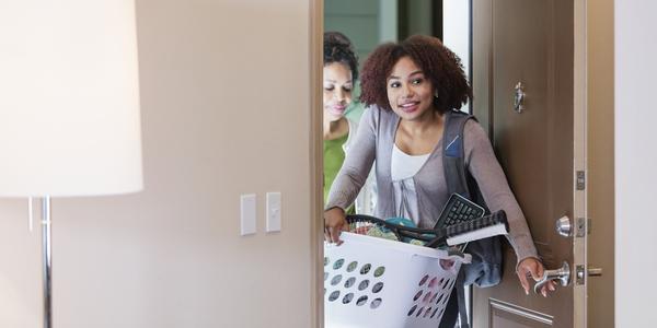Twee jonge vrouwen openen de deur van een appartement.