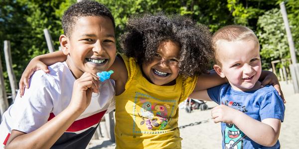 3 lachende kindjes in speeltuin
