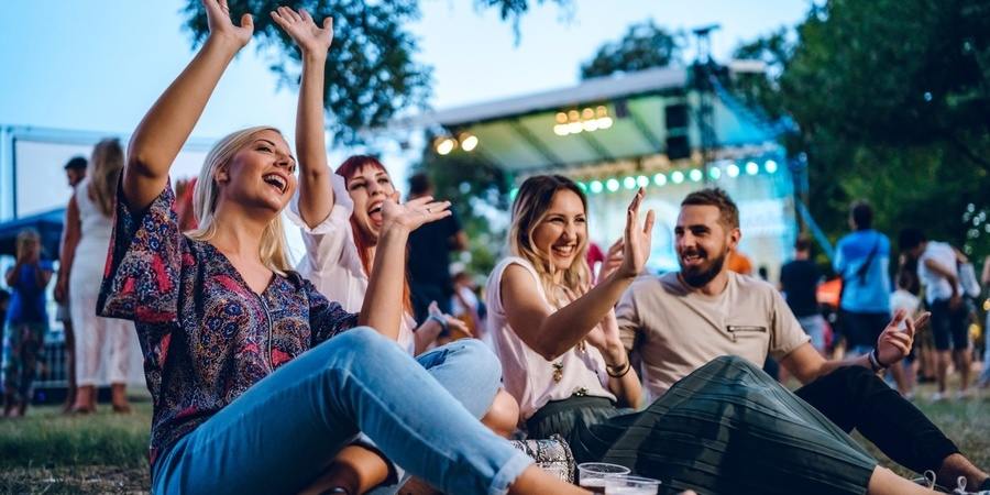 4 mensen genieten van een openluchtconcert terwijl ze neerzitten.