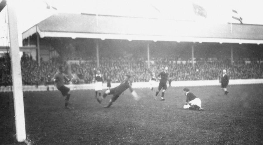Sfeerbeeld voetbalmatch Olympische Spelen 1920: 6 spelers waarvan 1 op doel schiet