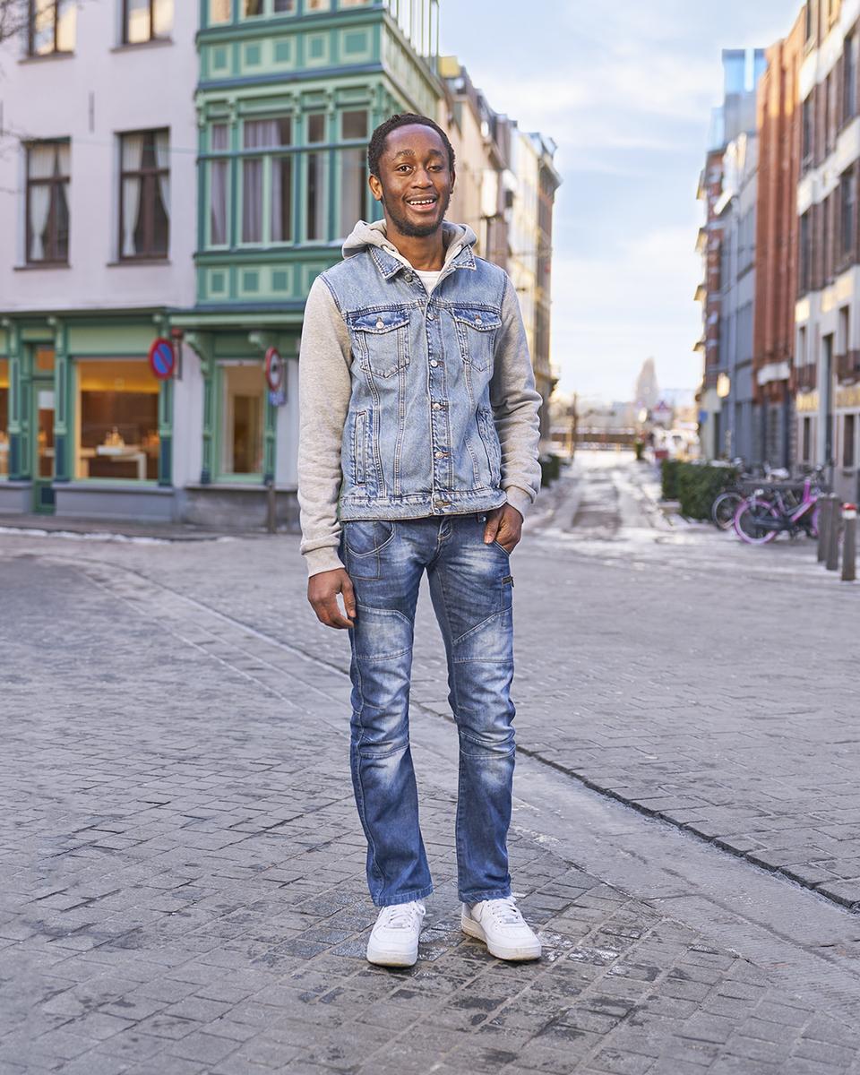 Emmanuel poseert lachend op straat voor de camera