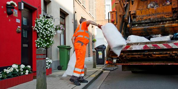 Een huisvuilophaler gooit afvalzakken in de vuilniswagen