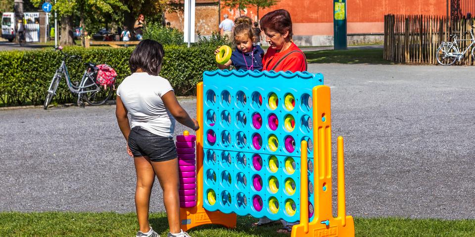 Een familie speelt met een reuze 4 op een rij-spel