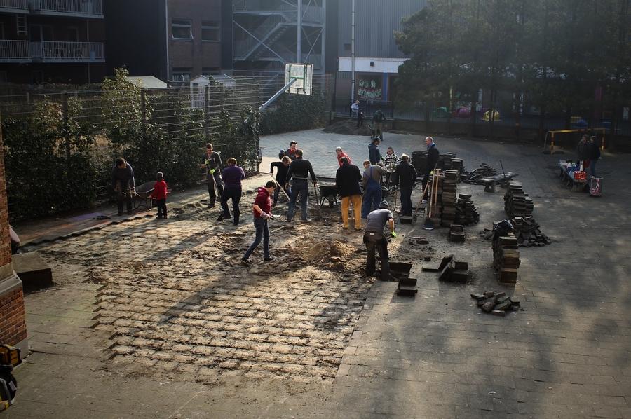 Een groep mensen haalt dals uit de speelplaats