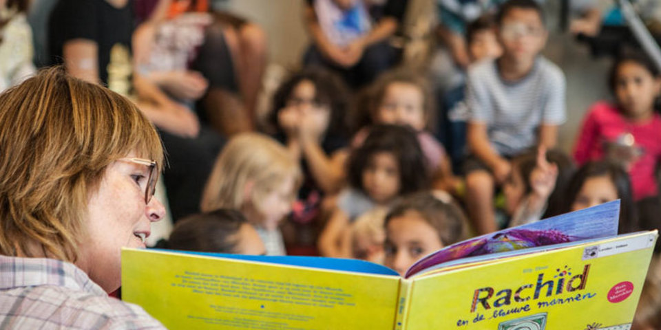 Vrijwilliger leest voor in bib Bist