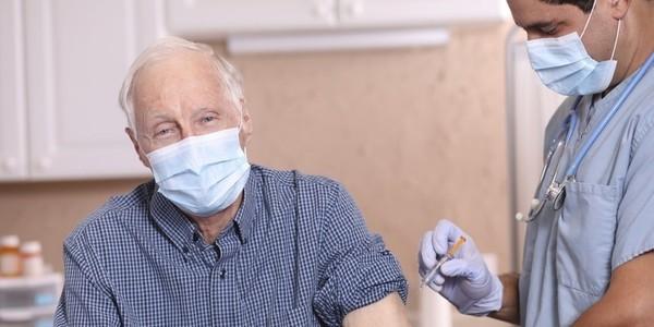 Foto van een oudere man die een griepspuit krijgt toegediend van een verpleegkundige of arts.