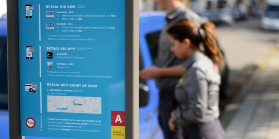 parkeerwachters staan achter een bord met meer info over de parkeerzone