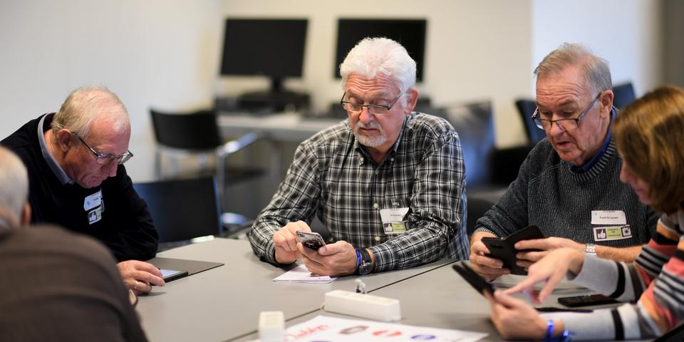 Drie DCA's werken op hun smartphone tijdens een workshop.