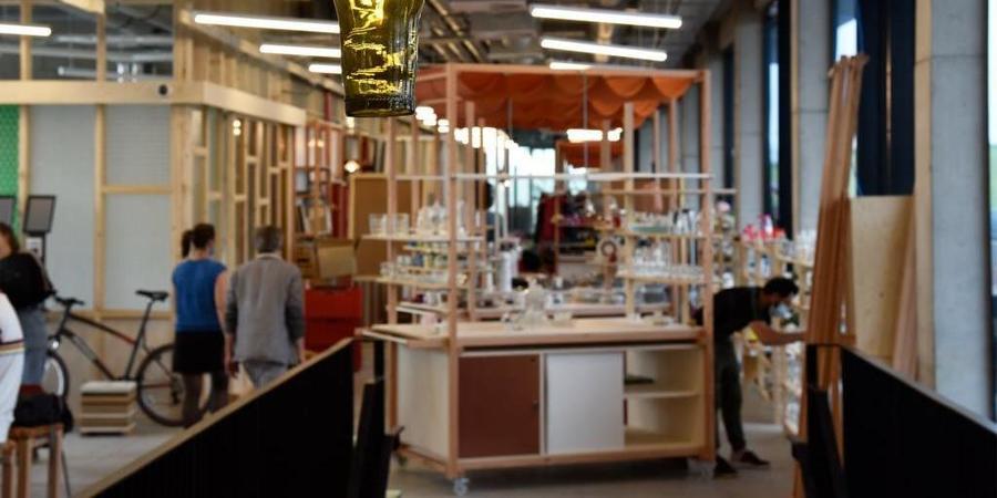 Verschillende mensen wandelen door een ruimte met meubels en andere producten.