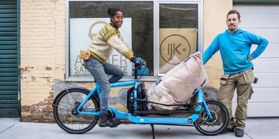 Vrouw en man op bakfiets vervoeren tuinafval