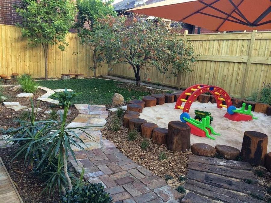 Kleine tuin met natuurlijke zandbak, verschillende paadjes en verschillende ondergronden