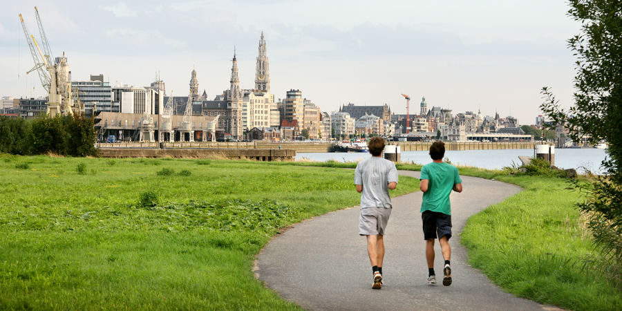 2 mannen joggen met de Antwerpse skyline op de achtergrond