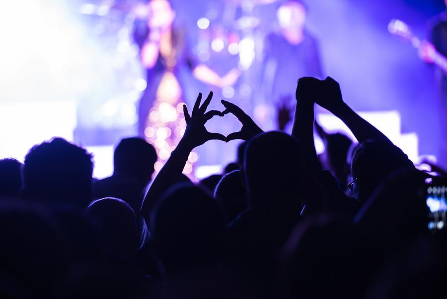 Iemand in het publiek vormt een hartje met de handen, performers flou op de achtergrond