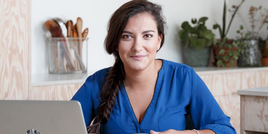 Een vrouw werkt aan de computer en kijkt in de camera.