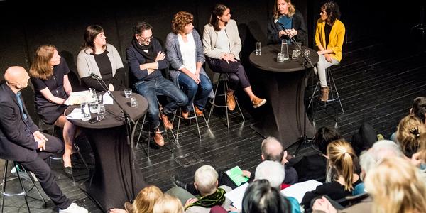 Deelnemers aan het panelgesprek over leesbevordering in het auditorium van Permeke