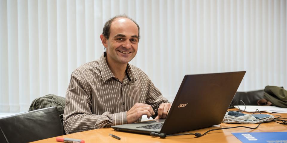 Man met laptop aan een bureau