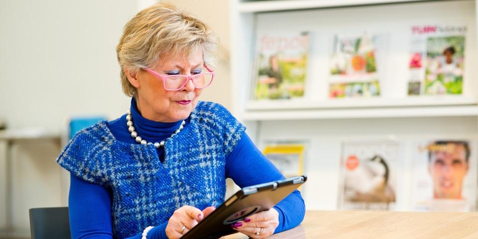 Vrouw leest op het nieuws op een tablet in de bibliotheek
