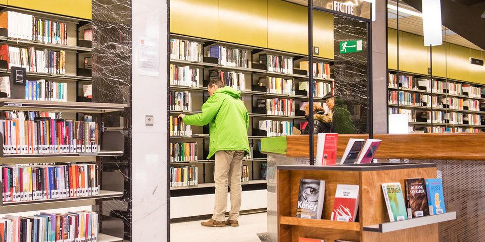 Bezoeker zoekt een boek in bib Driehoek