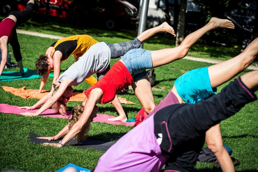 Groep vrouwen staan op handen en voeten (yoga oefening) in het park