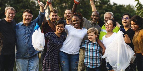 Een groep enthousiaste mensen met hun handen in de lucht.