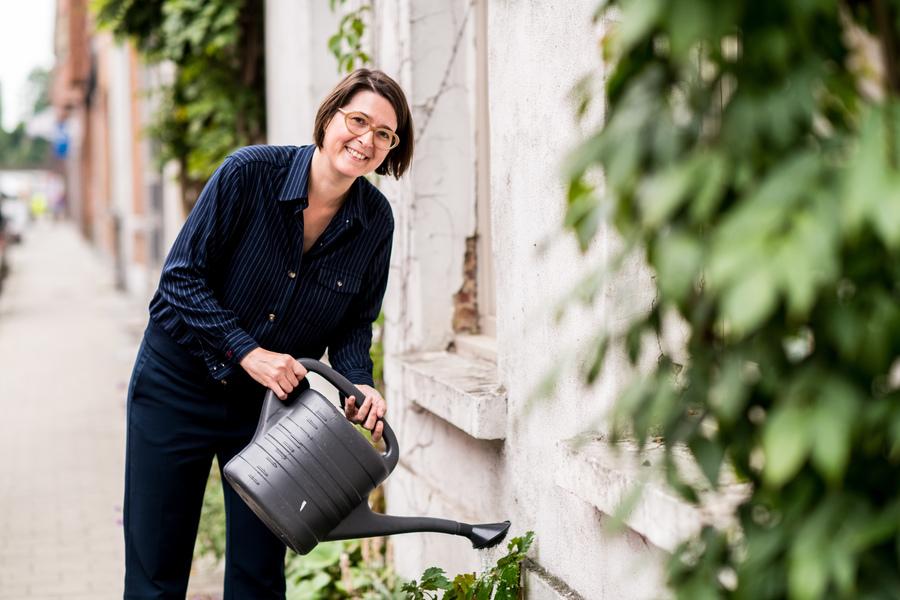 Foto van vrouw die met gieter geveltuintje water geeft