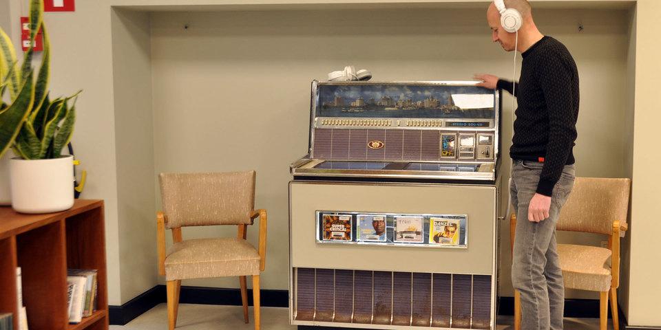 Bezoeker luistert naar de digitale jukebox in bib Driehoek
