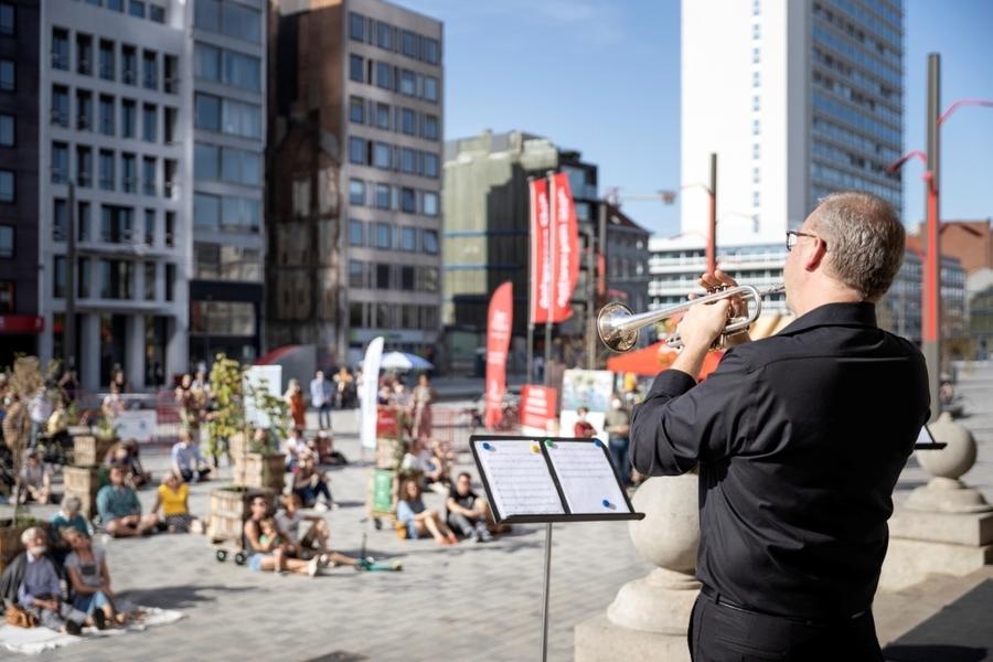Man speelt trompet met op de achtergrond publiek