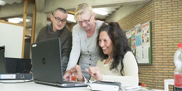 Drie mensen werken met de computer.