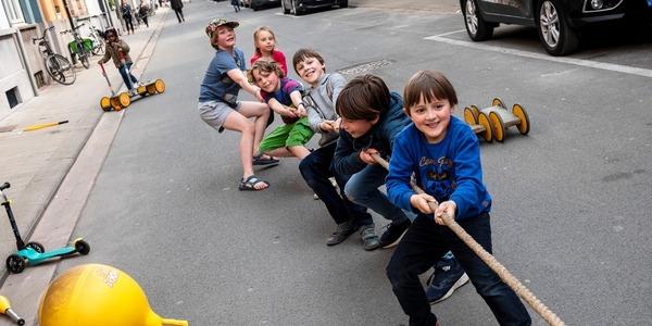 Foto van kinderen die touwtrekken in een speelstraat