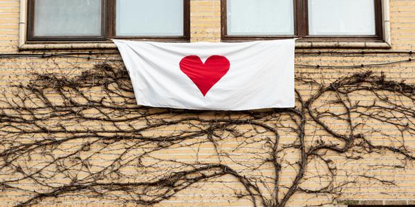 Witte doek met een rood, geschilderd hart hangt uit het bovenraam van een huis