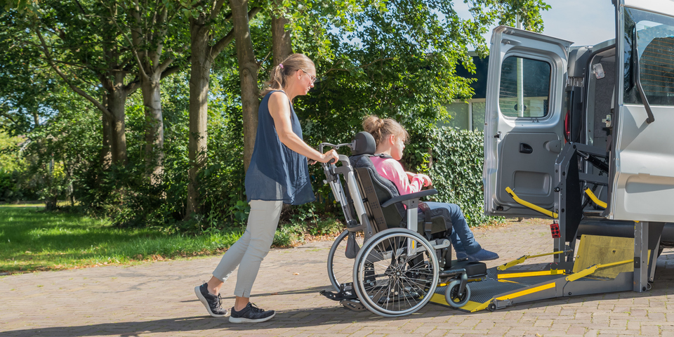 Een vrijwilliger helpt een rolstoelgebruiker.