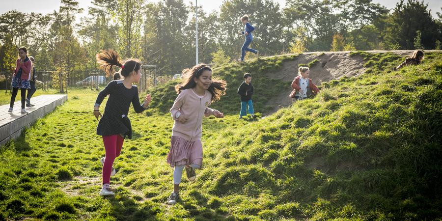 Kinderen rennen over heuvels en het gras