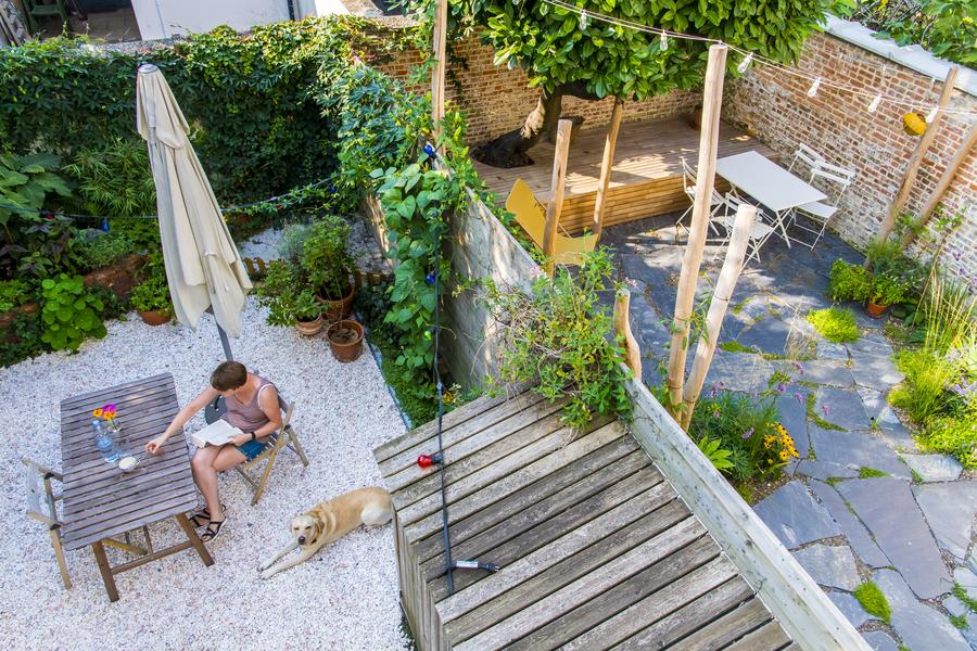 Bovenaanzicht van kiezeltuin en de tuin van de buren, een soort koer van natuursteen met brede voegen.
