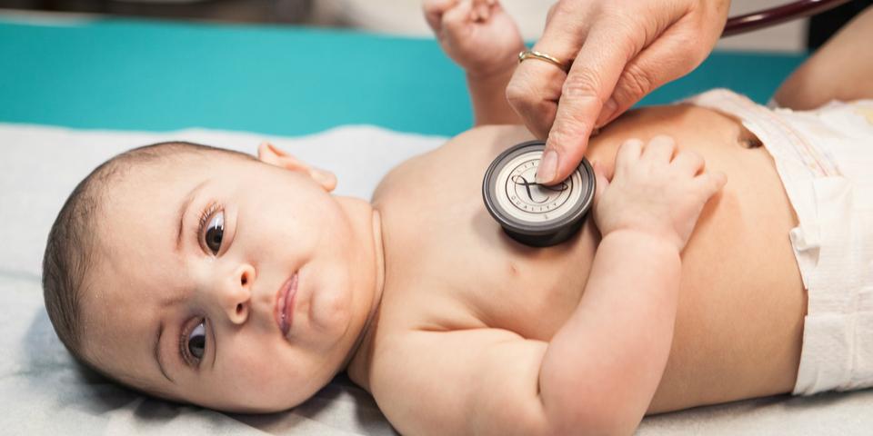 Een baby wordt onderzocht door een dokter.