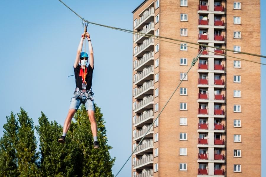Een man komt langs een kabel naar beneden vanaf een appartementsgebouw