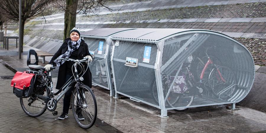 Bewoner met fiets bij fietstrommel