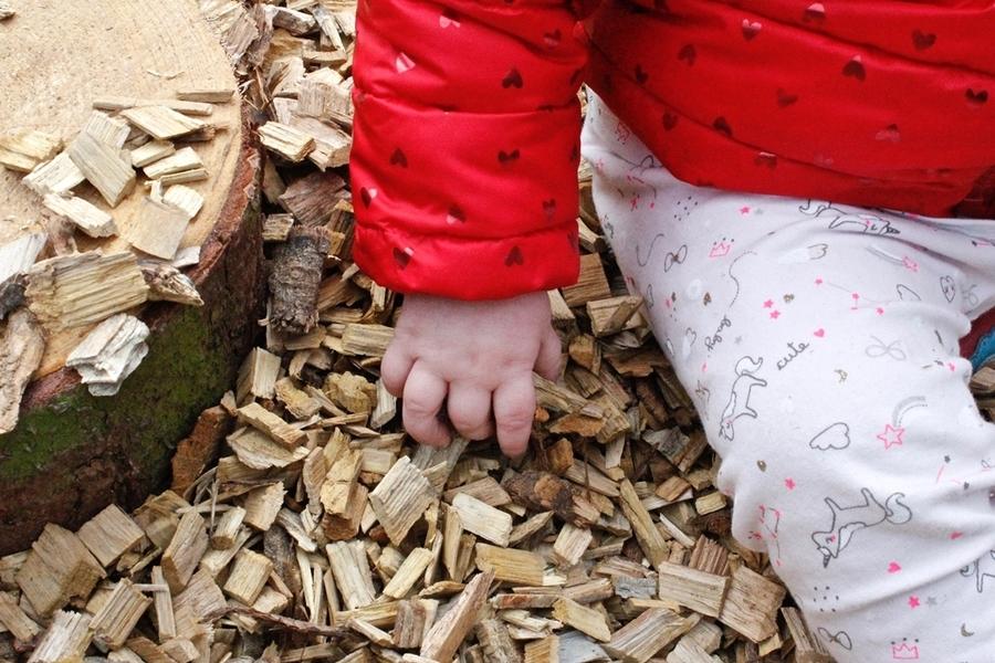 Baby voelt aan houtsnippers