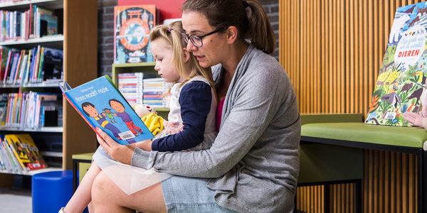 Een mama leest voor aan haar dochtertje in bib Driehoek
