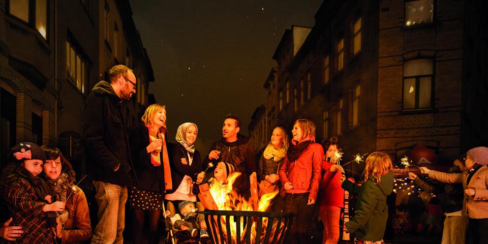 Straatbewoners staan gezellig rond een vuurkorf