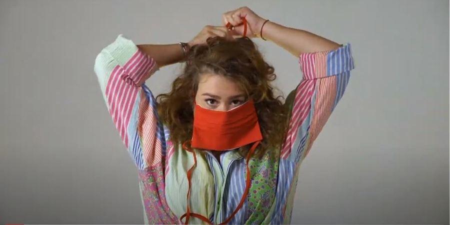 Een mevrouw doet een mondmasker rond haar gezicht.