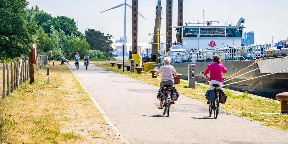 Verschillende mensen fietsen op een fietspad langs de Schelde. Op de achtergrond een binnenvaartschip en de haven.