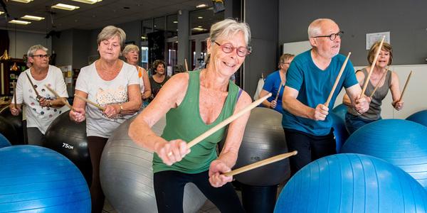 vijftigers (mannen en vrouwen) slaan met drumstokken op een yogabal