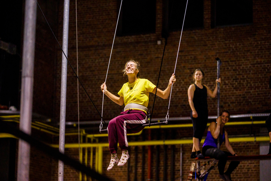 Dame zit lachend op een trapeze