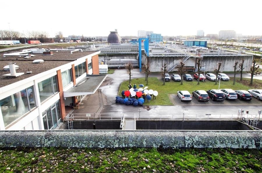 Foto vanop het dak van Aquafin dat helaas niet geschikt is voor een klimaatrobuust dak. De medewerkers van Aquafin houden een paraplu vast op de begane grond.