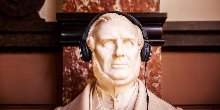 Beeld van een buste met een koptelefoon op zijn hoofd.