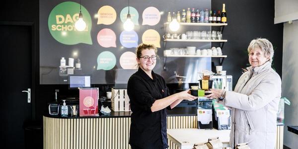 medewerker buurtrestaurant Dagschotel geeft maaltijd aan klant