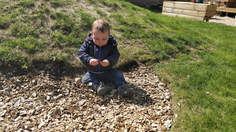 Kind voelt aan houtsnippers