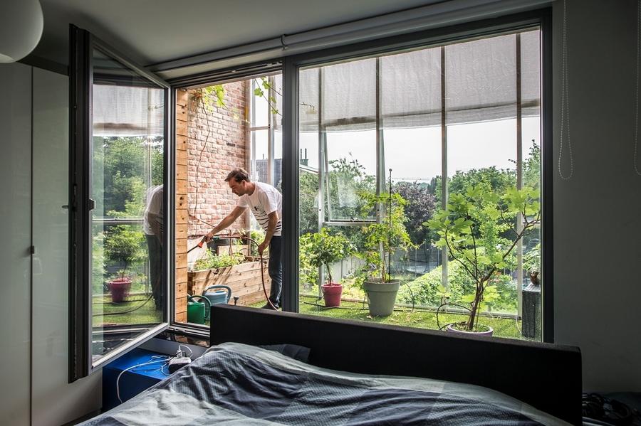 We zien een slaapkamer en een raam dat uitgeeft op een extra, groene buitenruimte.